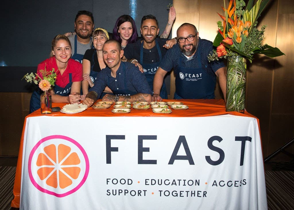 Sweetfin Chef Dakota Weiss (center) with FEAST's collaborating chefs at FEAST's 2019 Fall fundraiser leaning over a table with plated food.